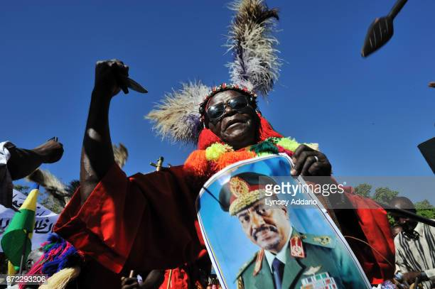 Sudanese traditional dancer holds up a poster of President Omar alBashir addresses as tens of thousands of supporters gather at a rally in downtown...