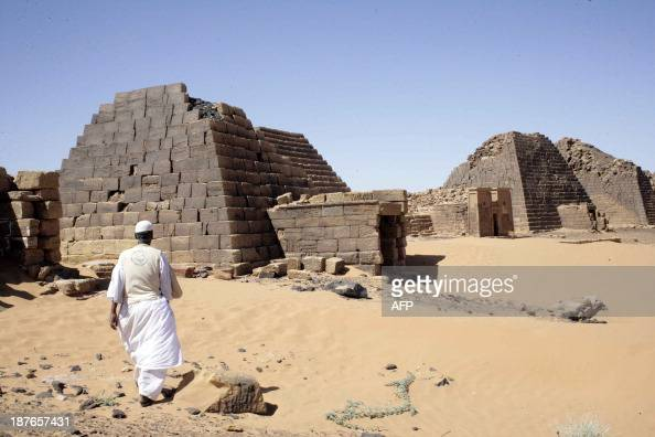 A Sudanese walks on November 10 2013 towards pyramids in the cemetary of Meroe north of Khartoum Sudan The Meroe dynasty the last in a line of 'black...