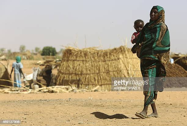 A Sudanese woman carries a baby at the Zam Zam camp for Internally Displaced People North Darfur on April 9 2015 Sudan heads to the polls next week...