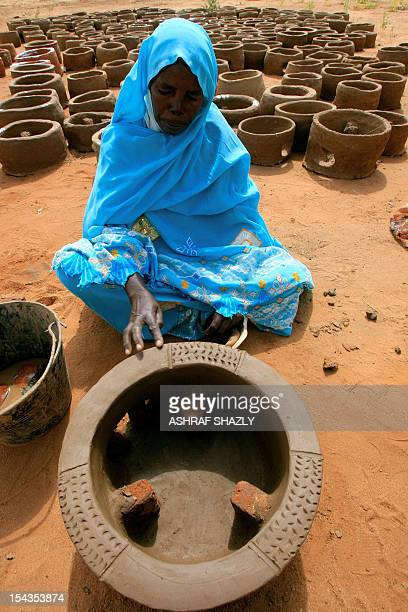 A Sudanese woman demonstrates the making of a traditonal clay pot during the visit of European Union ambassadors to the camp for internally displaced...