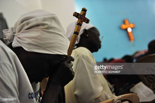 A Sudanese woman holds a cross as she prays during Sunday service in a church in Juba on January 16 one day after the historical weeklong...