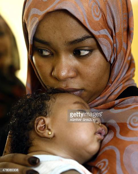 A Sudanese woman holds her baby as she waits for an inoculation against measles at the Samir Medical Clinic in the Sahafa neighbourhood of the...