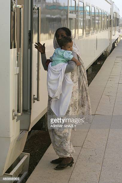 Sudanese woman holds her child as she boards the new Nile Train in Khartoum on March 17 2014 In a dilapidated povertystricken country where some...