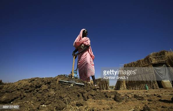 A Sudanese woman looks on as she works at the Zam Zam camp for Internally Displaced People North Darfur on April 9 2015 Sudan heads to the polls next...