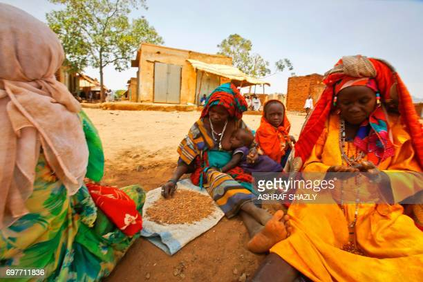 A Sudanese woman nursing a child eats with other women in the shade of a tree in the wartorn town of Golo in the thickly forested mountainous area of...