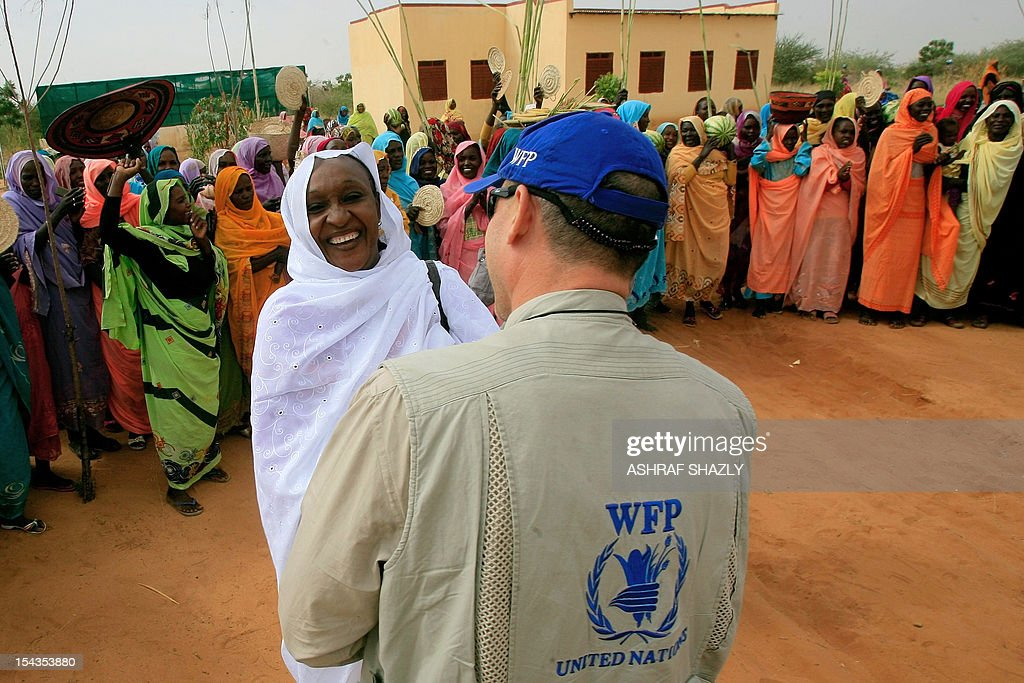 A Sudanese woman speaks with a member from the World Food Program (WFP) during the visit of European Union ambassadors to the camp for internally displaced person's (IDP) near the city of al-Fasher, in North Darfur, on October 18, 2012.