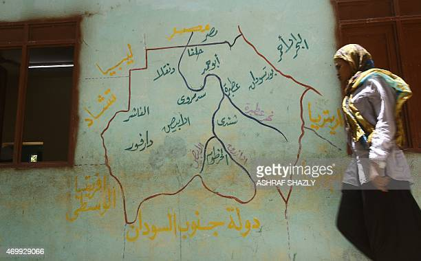 A Sudanese woman walks past a map of South Sudan painted on a wall at a polling station in the capital Khartoum on April 16 2015 Sudan extended...