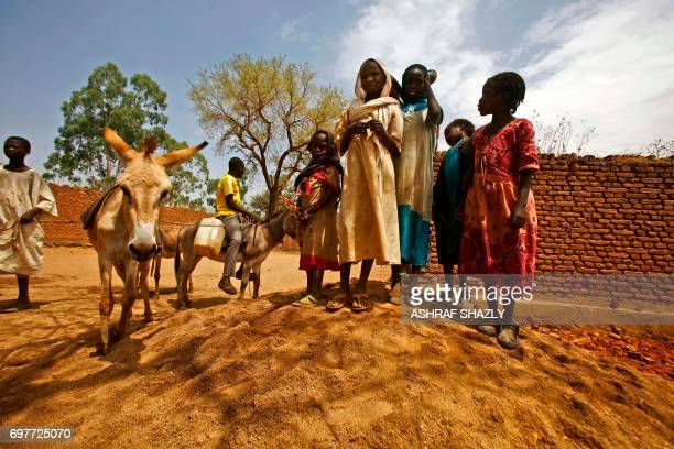 TOPSHOT Sudanese women and children stand next to a donkey in the wartorn town of Golo in the thickly forested mountainous area of Jebel Marra in...