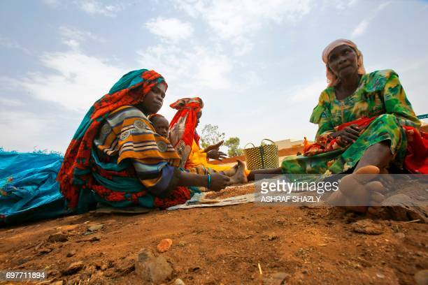 Sudanese women eat in the shade of a tree in the wartorn town of Golo in the thickly forested mountainous area of Jebel Marra in central Darfur on...