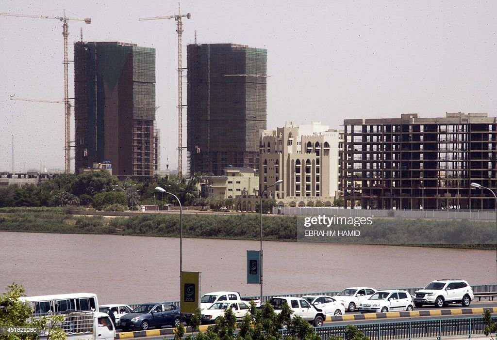 Sudaneses drive past buildings under construction in downtown Khartoum on June 23 as the country marks twentyfive years since Field Marshal Omar...