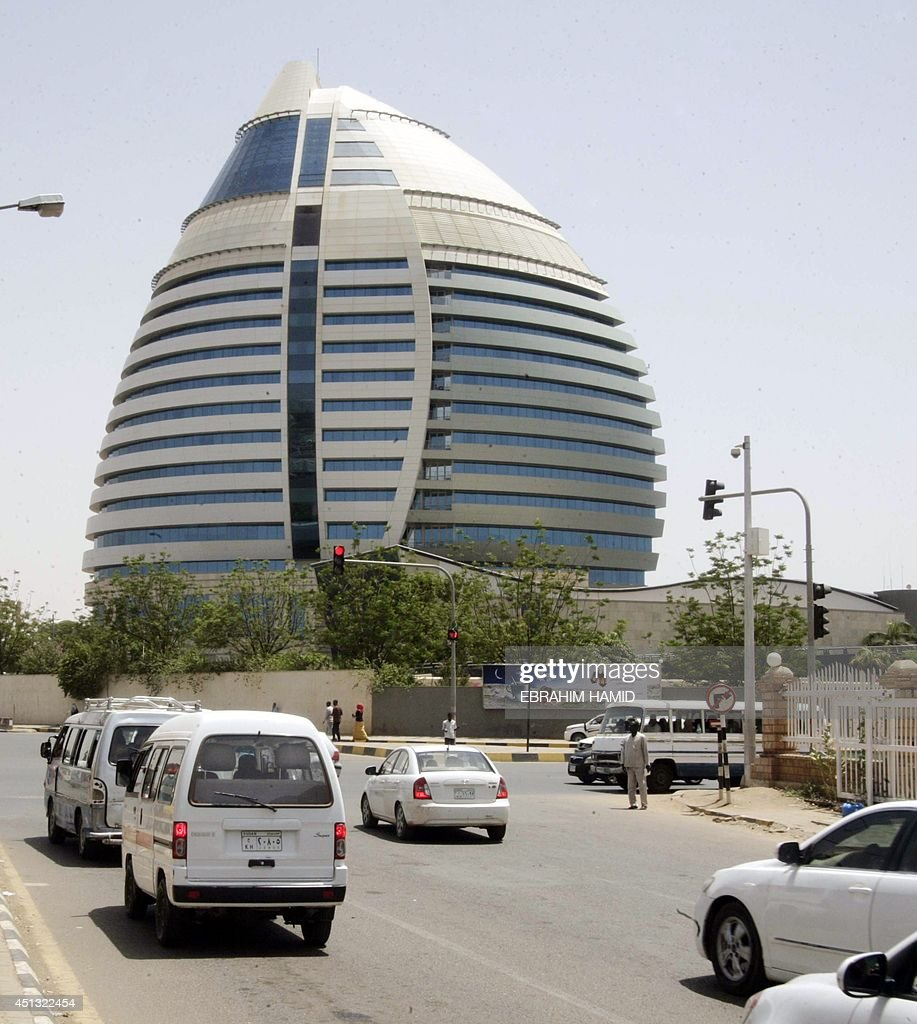 Sudaneses drive past the AlFateh tower in downtown Khartoum on June 25 as the country marks twentyfive years since Field Marshal Omar alBashir took...