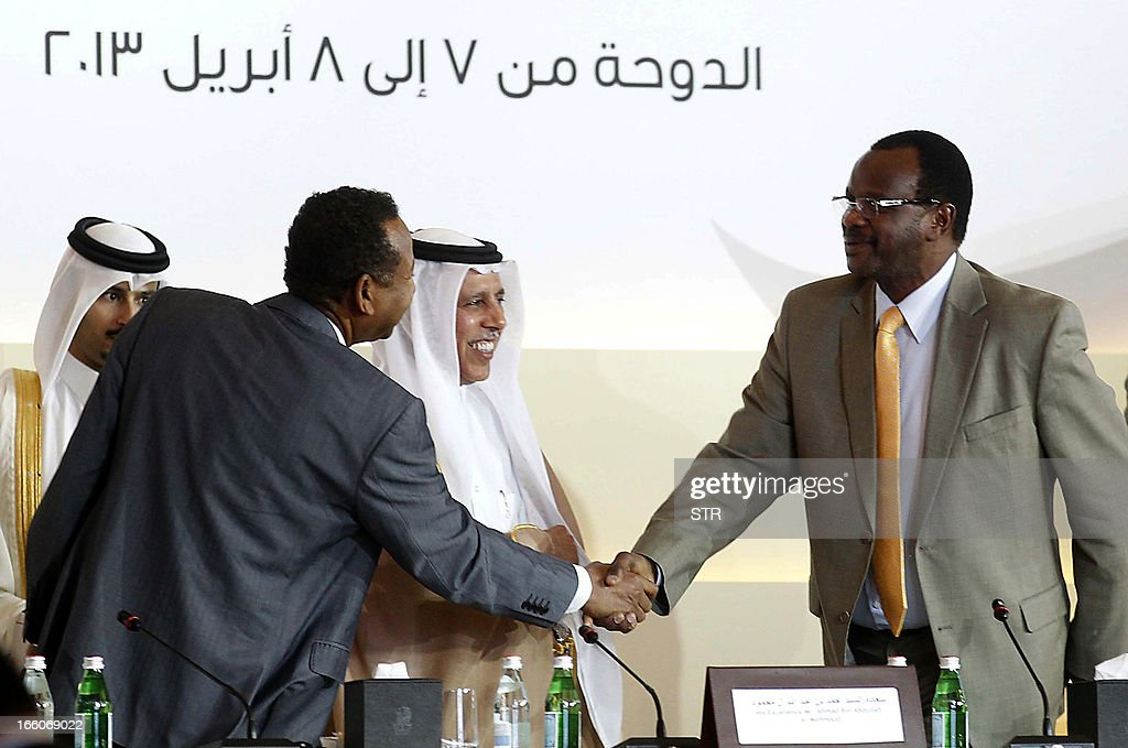 Sudan's Liberation and Justice Movement leader Eltigani Seisi (R) shakes hands with Sudanese presidential adviser Mustafa Osman Ismail (L) during the International Donor Conference for Reconstruction and Development in Darfur, in Doha on April 8, 2013. The Darfur donor conference has raised $3.6 billion in pledges to finance the development of war-ravaged Darfur in west Sudan, mostly from Khartoum itself, host country Qatar which contributed $500 million. AFP PHOTO/STR