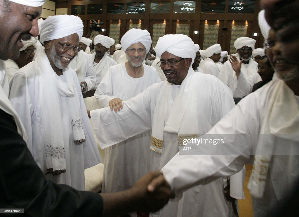 Sudan's President Omar alBashir greets supporters while Hassan alTurabi a leading Islamist figure behind the 1989 coup that brought Bashir to power...