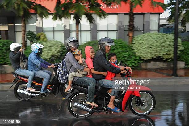 A sudden downpour catches Indonesian families traveling on motorcycle during the Eid alFitr holiday in Jakarta on September 11 2010 Indonesian...