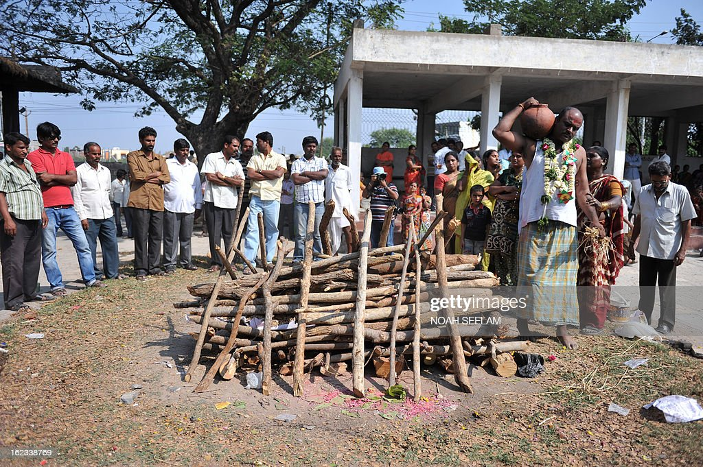 Sudhakar Reddy, (R) brother of the deceased performs the last rites for bomb blast victim Swapna Reddy at a crematorium in Hyderabad on February 22, 2013. Indian police revealed Friday they had been warned of a possible attack by Islamist militants in a bustling shopping area of Hyderabad where twin bombings killed at least 14 people and wounded scores. AFP PHOTO / Noah SEELAM