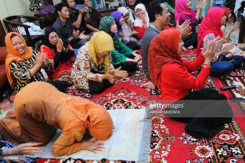 Sudjiatmi the mother of Indonesian presidentelect Joko Widodo bows following an announcement by Indonesia's General Election Commission confirming...