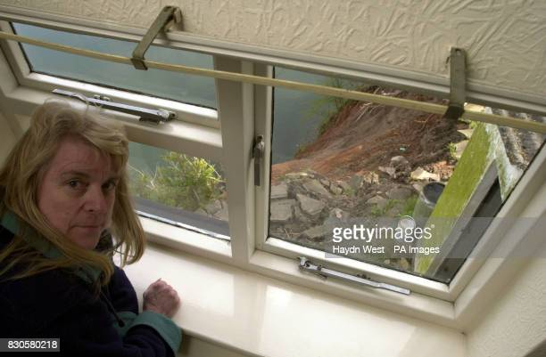 Sue Astill peers into a huge hole which opened up when nearly 8ft of her garden patio slipped into a quarry beneath Mrs Astill cheated death at her...