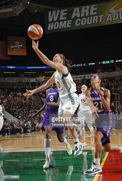 Sue Bird of the Seattle Storm goes to the basket against Ticha Penicheiro and DeLisha MiltonJones of the Los Angeles Sparks during the game on August...