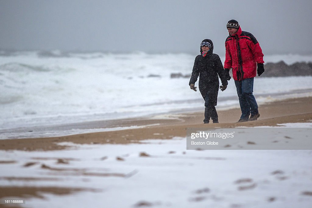 Sue Collins, left, and her husband Mike Collins of Newbury, walk along the beach on Plum Island as a large winter storm approaches.