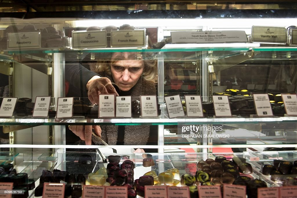 Sue Geibel restocks chocolates at the Chocolate Moose on February 12, 2016 in Washington, DC. Valentine's Day is observed on February 14. / AFP / Brendan Smialowski