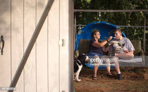 Sue Landreth feeds her son a potato salad during a recent family cookout while dog Molly looks on Ethan Poulin has autism spectrum disorder and...
