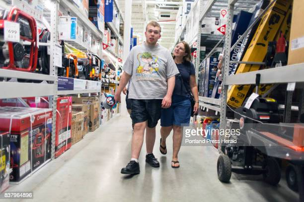 Sue Landreth guides her son Ethan Poulin through Lowe's Home Improvement during a weekly visit Poulin has autism spectrum disorder and intermittent...