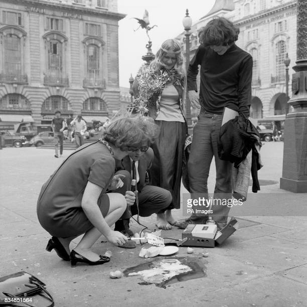 Sue McGregor and Charles Stokes reporters for radio's 'World At One' programme are watched by a couple of bystanders as they carry out a test to fry...