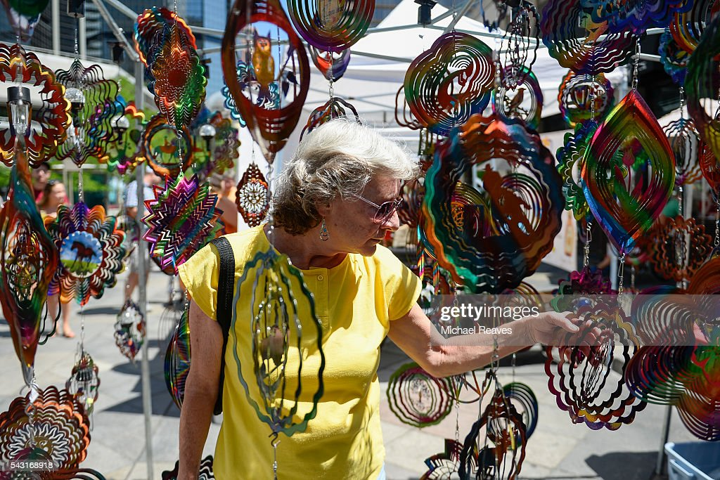 Sue Peterman walks through a display at the Designs in the Wind booth during the 16th St. Street Fair on June 26, 2016.