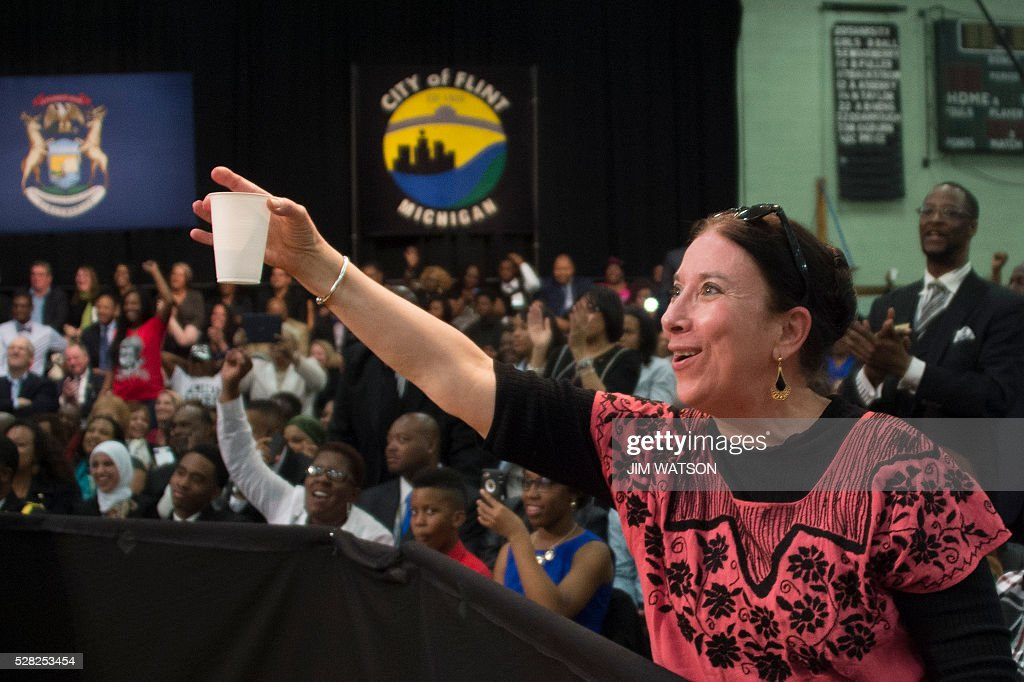 Sue Quintanilla offers US President Barack Obama a glass of water as he speaks at Flint Northwestern High School in Flint, Michigan, May 4, 2016 after meeting with locals for a neighborhood roundtable on the drinking water crisis. / AFP / Jim Watson