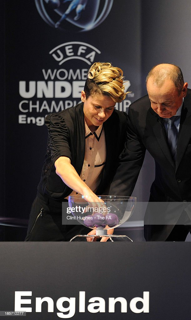 Sue Smith (L) draws a ball from the pot whilst Mikael Salzer, UEFA Head of Women's and Futsal Competitions looks on during the UEFA European Women's Under 17 Championship Draw at Burton Town Hall on October 24, 2013 in Burton upon Trent, England
