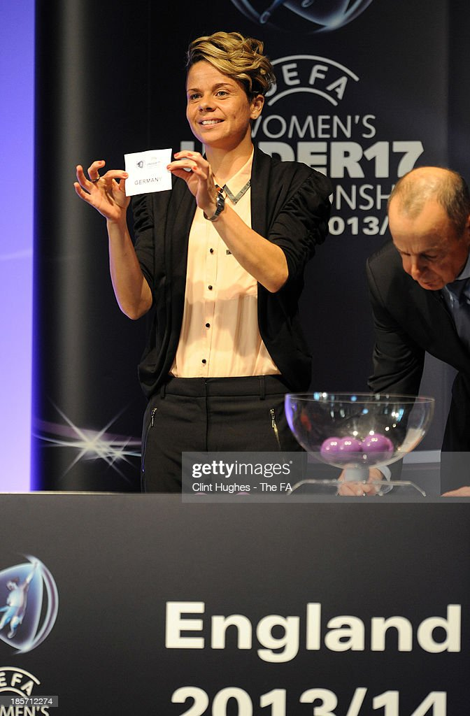 Sue Smith (L) draws a team from the pot whilst Mikael Salzer, UEFA Head of Women's and Futsal Competitions looks on during the UEFA European Women's Under 17 Championship Draw at Burton Town Hall on October 24, 2013 in Burton upon Trent, England