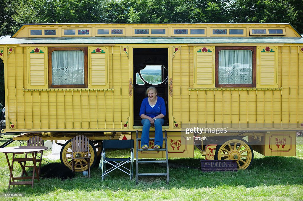 Sue Smith from Dalton near Thirsk sits on the steps of her caravan at the steam rally at Duncombe Park on July 7, 2013 in Helmsley, England. The popular steam rally takes place in the magnificant grounds of the park over the first weekend of July each year and brings together traction engines, working displays, vintage tractors, commercial and military vehicles, vintage cars and motorcycles.