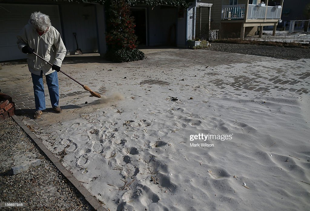Sue Vehslage sweeps sand off her driveway that was washed in by Superstorm Sandy, on November 24, 2012 in Long Beach Island, New Jersey. New Jersey Gov. Christie estimated that Superstorm Sandy will cost New Jersey $29.4 billion in damage and economic losses.
