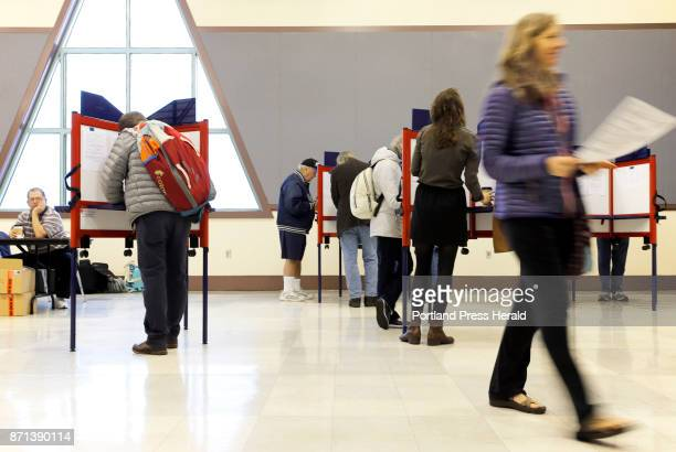 Sue Vittner right walks her completed ballot to the scanning booth at the Merrill Auditorium voting station Tuesday morning Turnout at the station...