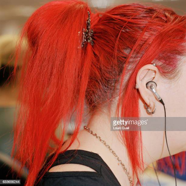 Sue Williams out bound call centre agent demonstrates her individuality in the colour of her red hair while making calls from her office desk in...