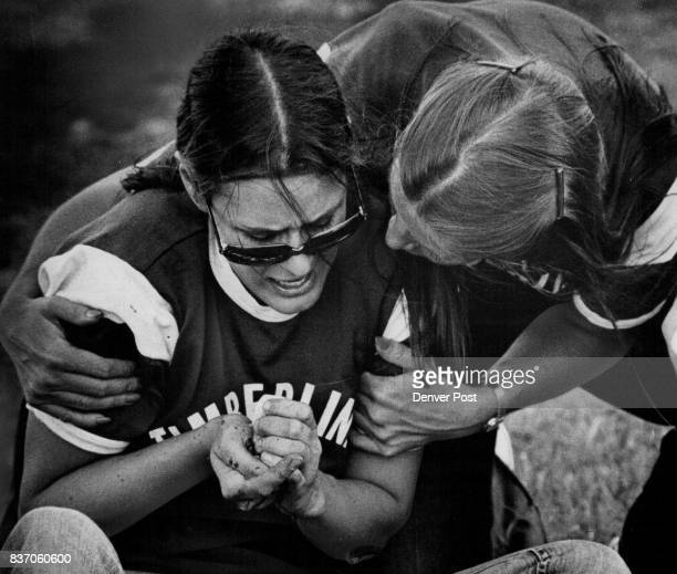 Suffering a fractured finger and torn nail from catching a fly ball Line left is comforted by Arlene Korte Both are members of TTC's women's softball...