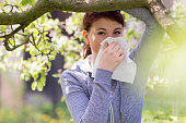 Young woman suffering from Pollen allergy, alergy season, Girl blowing her nose