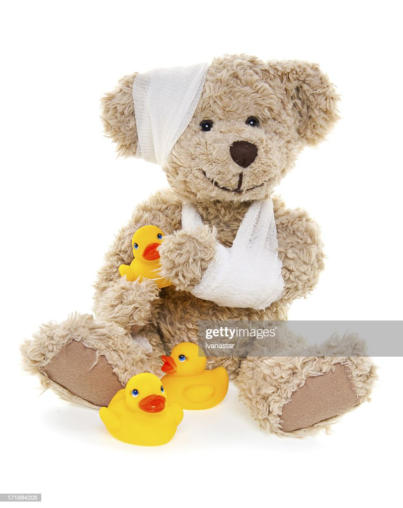suffering injured sweet teddy bear with rubber ducks stock photo