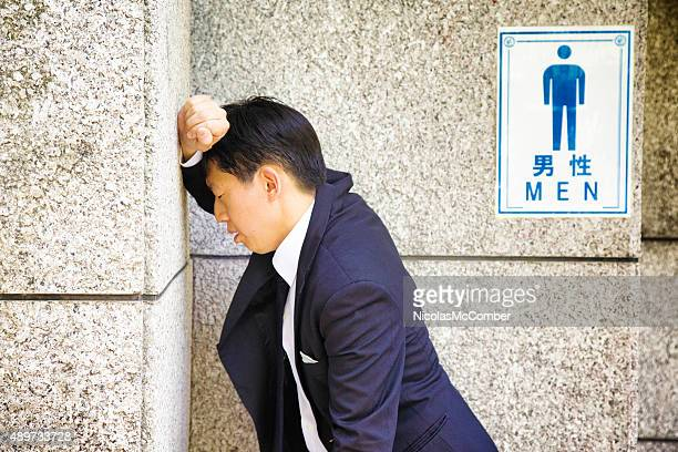Suffering Japanese businessman rests against WC wall feeling sick