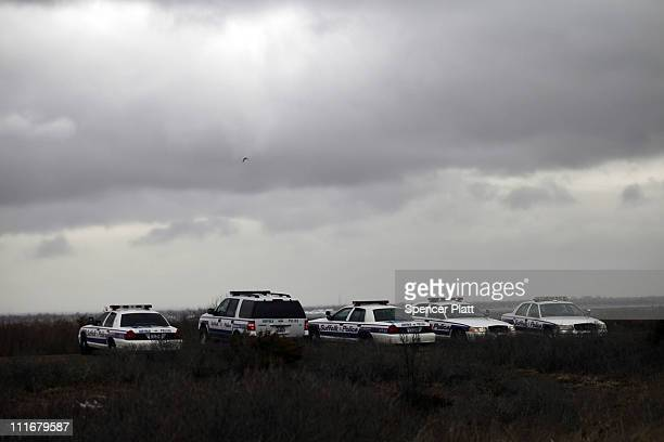 Suffolk County Police cars involved in the search effort are parked on the side of the road along a stretch of beach highway where police recently...