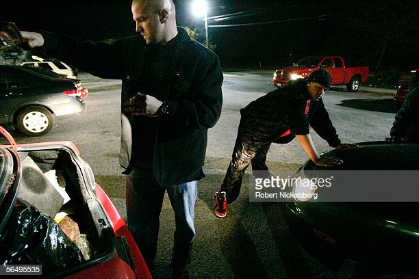 Suffolk County Police officers from the antigang unit check the trunk of a car for marijuana in a local shopping mall on eastern Long Island October...