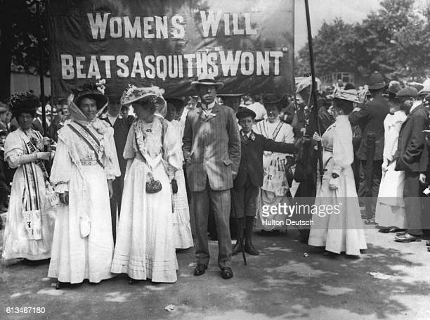 Suffragettes dressed in their white uniforms carry a banner at the funeral of their fellow campaigner Emily Davison who died making a protest at the...
