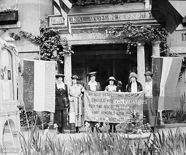Suffragettes hold up banner in front of a building that has an architrave sign of the National Woman's Party They claim to be ignored by the...