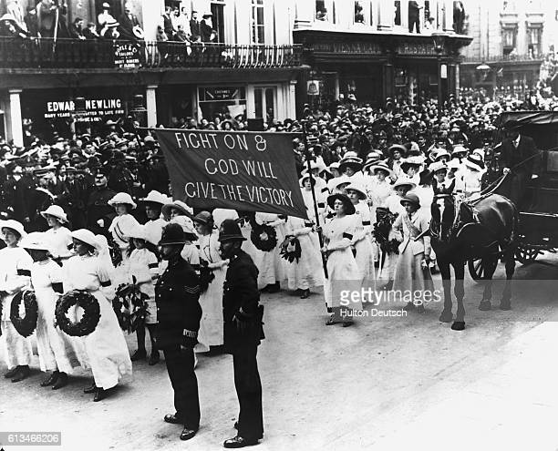 Suffragettes in white uniform form part of the procession at the funeral of militant campaigner Emily Davison who died making a protest at the 1913...