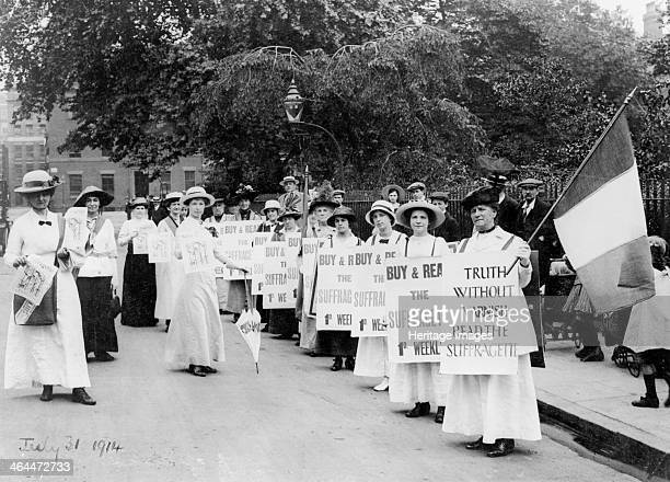 Suffragettes on a 'poster parade' selling the Suffragette 31st July 1914 The women carry newspaper satchels and flags and wear sandwich boards...