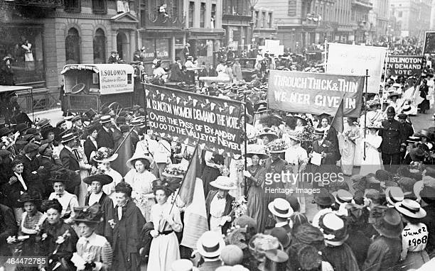 Suffragettes on their way to Women's Sunday 21st June 1908 Crowds line the street as the suffragettes parade past holding banners Two banners can be...