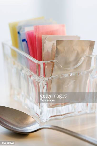 Sugar and sweetener packets next to spoon