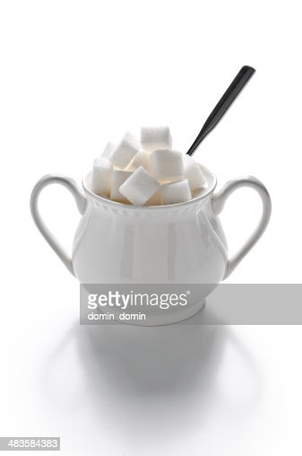 Sugar bowl full of sugar cubes and spoon, isolated on white