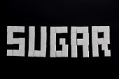Sugar cubes used to spell the word sugar on a black background