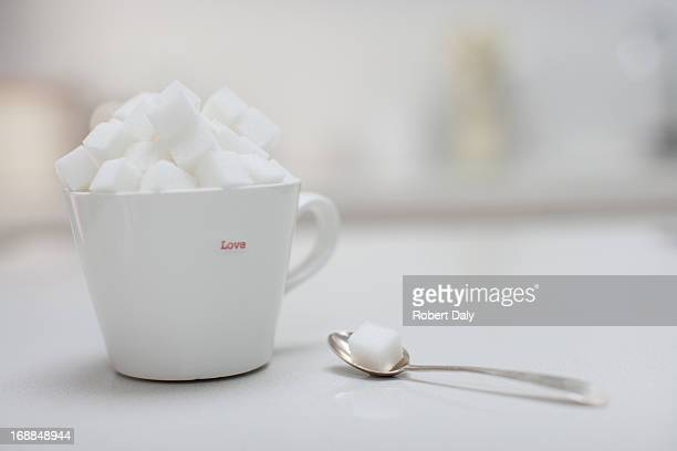 Sugar cubes filling coffee cup next to spoon with sugar cube